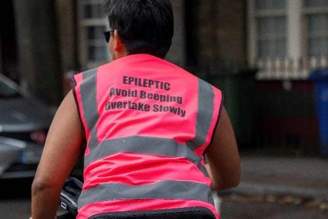 a cyclists in a high visibility bright pink cycling jacket facing away from us. The words 'Epileptic Avoid beeping overtake slowly' are written on the back of the jacket in bold text.