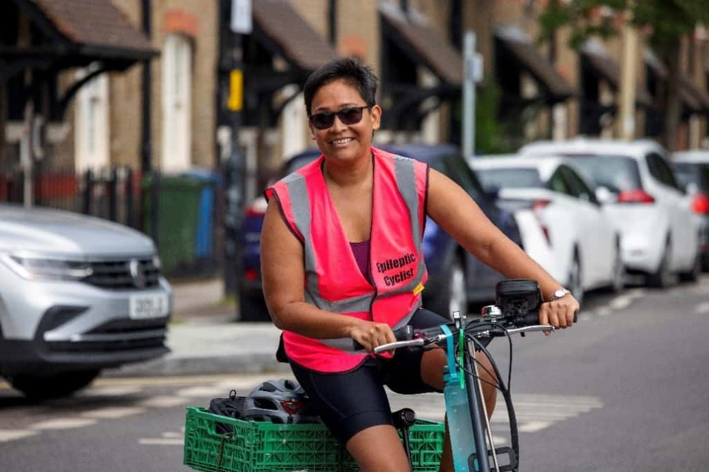 a cyclist in a bright pink vest smiles while cycling toward the camera