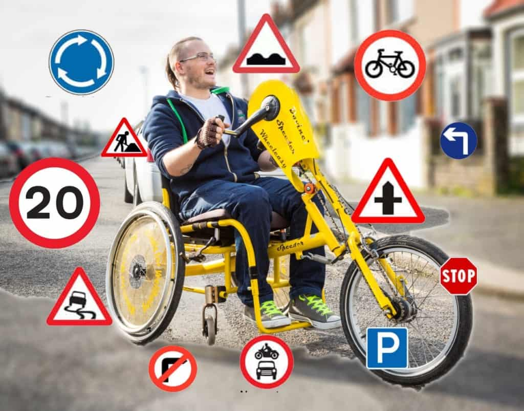 A smiling guy sits on a handcycle while road signs float around him.