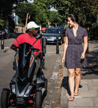 Image from CWIS2 Report. A man rides a mobility scooter on a residential road, talking to a women walking on the pavement.
