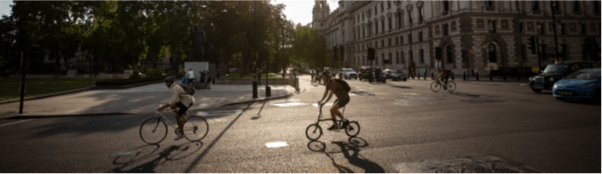 Image from CWIS2 Report. Two cyclists ride past Parliament Square, London.